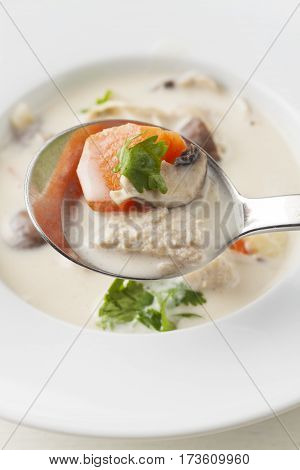 thai tom kha gai soup on a spoon