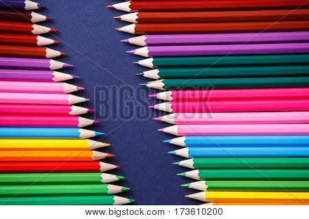 colored pencils isolated on blue background lying in opposite corners. Art and design. Painting and drawing. School and education.