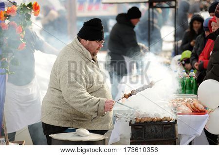 Orel Russia - February 26 2017: Maslenitsa fest. Oversized man cooking meat shashlik horizontal