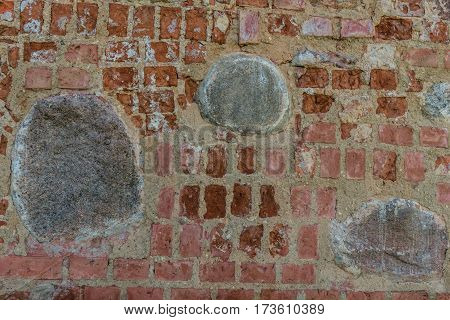 Restored medieval red brick wall with big old gray stones