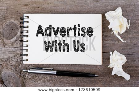 Advertise With Us. On a wooden table notebook and pen.