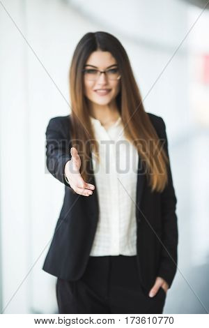 Business woman giving a hand. handshake in the office panoramic windows