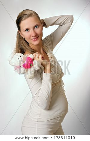 happy pregnant woman with toy on white background