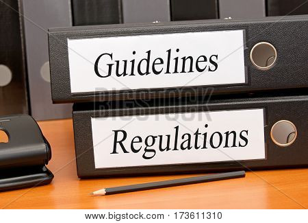 Guidelines and Regulations - two binders with text on desk in the office