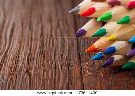 Colored pencils on a wooden board. Closeup view. Angle. Brown table. Drawing and painting. School and education. Artist. Art and design.