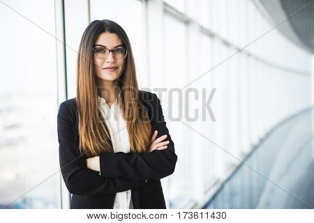 Businesswoman portrait. Businesswoman crossed hands portrait in office with panormic windows.