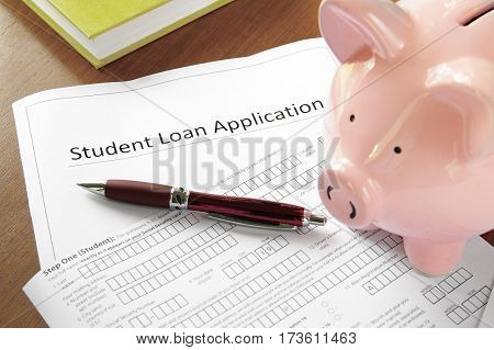 student loan application form with piggy bank and book