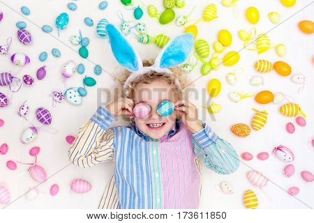 Funny little boy with bunny ears having fun on Easter egg hunt. Child playing with colorful Easter eggs. Kids play with pastel color rainbow eggs. Spring and Easter art and crafts for children.