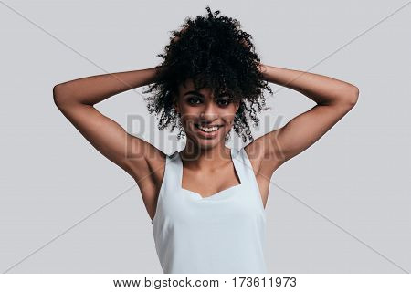 Young and beautiful. Attractive young African woman in casual wear keeping hands in hair and smiling while standing against grey background