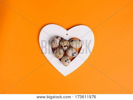 Quail Eggs In White Heart On The Orange Background