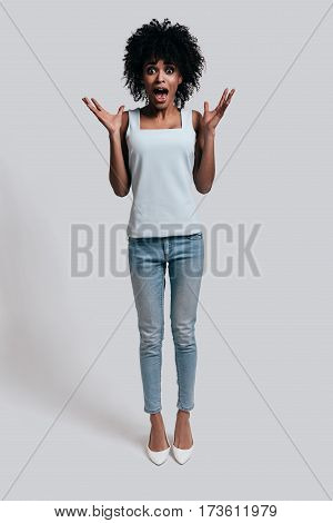 Shocked woman. Full length of shocked young African woman in casual wear gesturing with opened mouth while standing against grey background