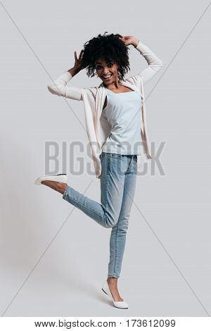 Playful woman. Full length of attractive young African woman in casual wear keeping hands in hair and looking at camera while standing against grey background