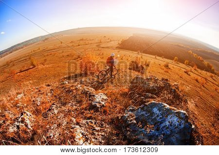 Cyclist Riding the Bike on the Mountain Rocky Trail at Sunset. Extreme Sports. Travel in the countryside. Fisheye and wide angle. Hill and rocks. Spring season.