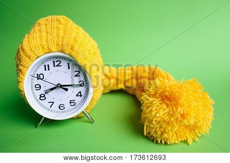 Alarm Clock In Yellow Hat On The Green Background