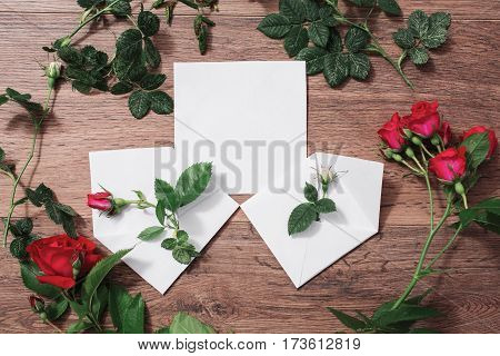 Open envelopes frame of red and white roses and red hearts on wooden background. Greeting card mockup. Conceptual photography. Wedding invitation card. Valentine day. Flat lay mockup top view copyspace. Mock up concept