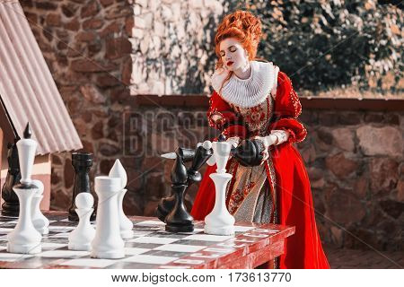 The Red Queen is playing chess. Red-haired woman in a chic vintage dress. Fashion Photo of Queen. Play chess concept