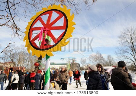 Orel Russia - February 26 2017: Maslenitsa fest. Pagan Kolovrat sign against blue sky with people background