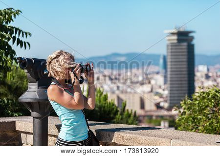 Female traveler standing with camera against the background of the port of Barcelona. Spain. Cute, smiling blond girl with curly hair in a blue t-shirt.