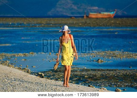Lonesome woman goes for a walk at sundown on the beach poster