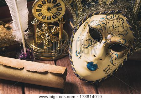 Literature concept. Still life with feather in inkstand scroll venetian mask old booksvintage clock and box on wooden table. Vintage toned image.