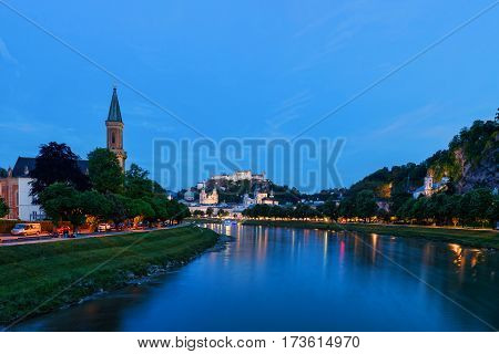 Late evening in Salzburg, salzach river with reflection and lights, tower church, ancient castle, Austria