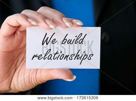 We build relationships - female hand with business card