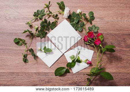 Open envelopes frame of red and white rose and red hearts on wooden background with rose. Greeting card with rose. Conceptual photography. Wedding invitation card. Valentine day. Flat lay rose top view copyspace mock up. Rose concept