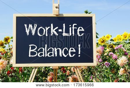 Work-Life Balance - easel in the summer garden with flowers in the background