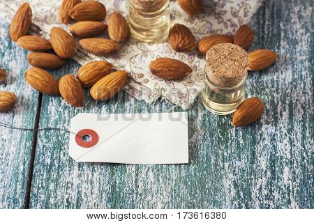 Almond Oil In Bottle  And Nuts On Wooden Background