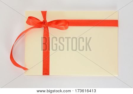 Light yellow envelope with a red ribbon isolated on a white background. For gift, present, surprise or invitation
