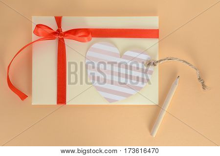 Light yellow envelope with a red ribbon, heart card and pencil isolated on apricot background. For gift, present, surprise or invitation