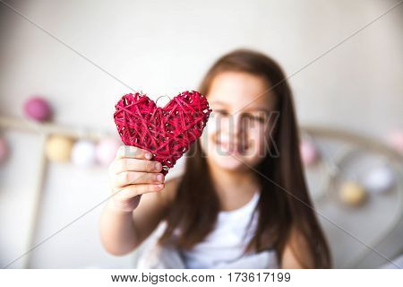 Beautiful little girl holding a red heart. Home comfort family people