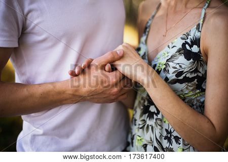 Hands close up. Loving couple in the forest on a sunny day. To love each other. Silhouettes of people Conceptual photo with hands. A man and woman hold each other's hands