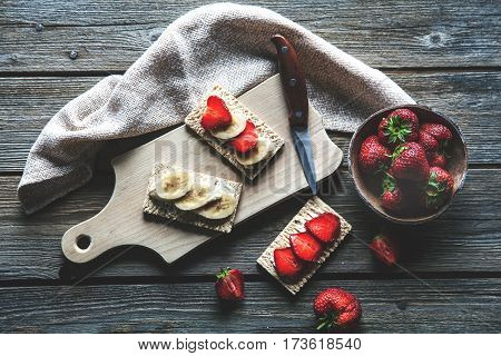 Fruity toast on wooden background. Strawberries bread butter and cheese.Vintage style