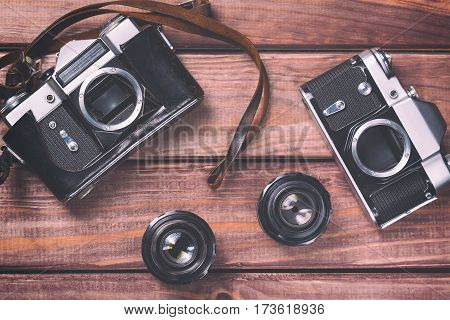 Old film camera with lenses and strap on wooden background. Vintage toned and top view.