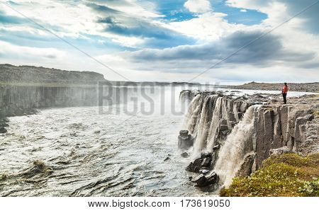 Beautiful View Of Woman Standing Near Famous Selfoss Waterfall In Vatnajokull National Park, Northea