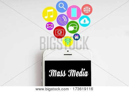 """Mass Media"" words on smartphone with social media icon with white background - business finance and copy space concept"