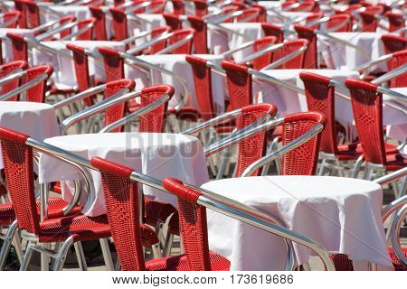 Close-up view of rows of empty red chairs and tables