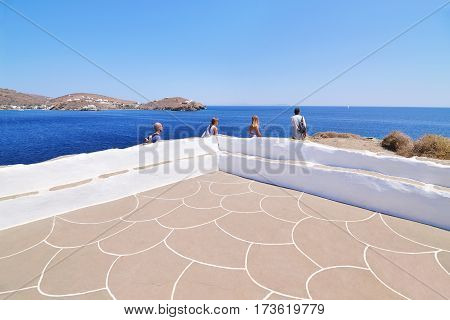 SIFNOS GREECE, AUGUST 28 2016: tourists looking the Aegean sea at Panaghia Chrisopigi church Sifnos Cyclades Greece. Editorial use.