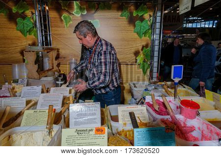 Moscow, Russia - February 25, 2017: Gray-haired man seller at the fair fills a jar with home produced honey for the buyer