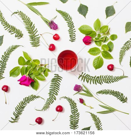 Red tea in a cup green blades of grass with purple flowers leaves birch twigs rose with red flowers green ferns ripe cherries lie on a white background. Flat lay top view. Herbal decoction. White cuo concept