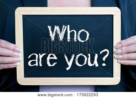 Who are you - businesswoman holding chalkboard with text