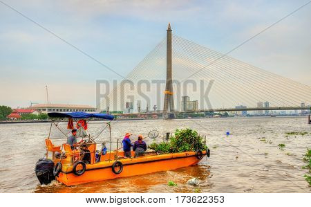 Boat cleaning the Chao Phraya river in Bangkok - Thailand