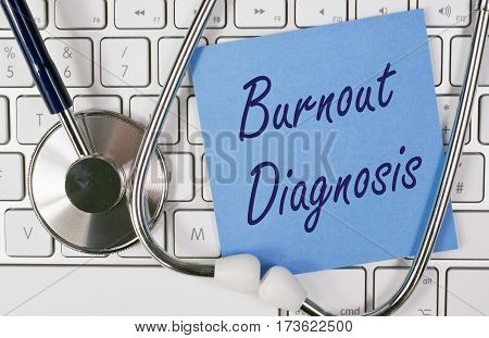 Burnout Diagnosis - blue note paper with text and stethoscope on computer keyboard