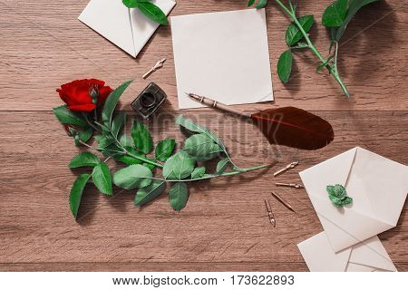 Fountain pen and ink on wooden background. White envelope and red roses. Greeting card. Conceptual photography. Wedding invitation card. Valentine day. Tips to pen. Flat lay copyspace mock up. Envelope concept