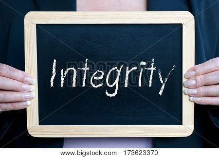 Integrity - Businesswoman holding chalkboard with text