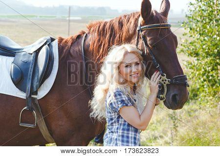 Beautiful blonde girl in plaid shirt hugging her brown horse.