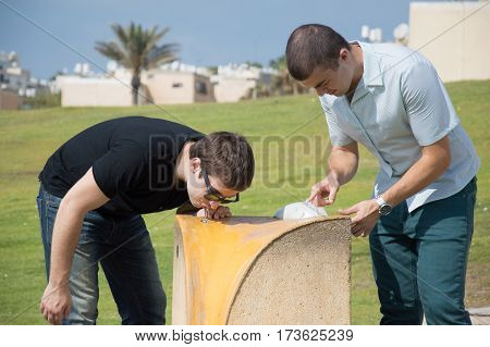 Two men drinking water from water fountain cooler in city park.