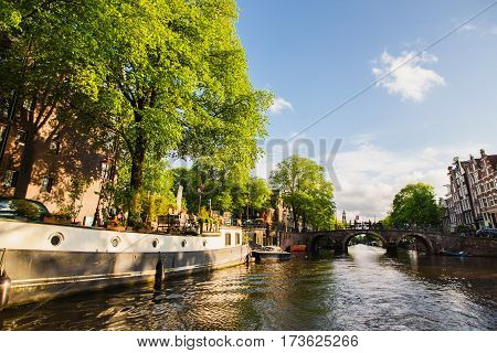 Spring sunny Amsterdam. The bright clear blue sky with white clouds. Boat trip on the canals of Amsterdam. The bridge over the water. Travel to Europe. Amsterdam in summer