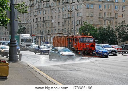 Moscow Russia - June 02 2016: Street flusher machine and vehicles riding on the road in the city. Watering machine washes the road dust and dirt